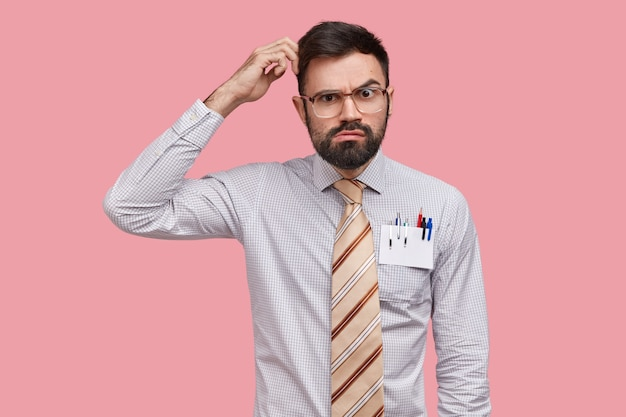 El diseñador masculino inseguro, vacilante, se rasca la cabeza y mira con expresión seria, piensa en un nuevo esqueleto, usa camisa formal, tiene bolígrafos y lápiz en el bolsillo