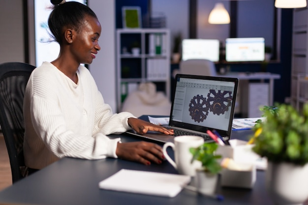 Diseñador mecánico africano que trabaja en la computadora a altas horas de la noche haciendo horas extraordinarias para terminar el proyecto