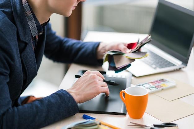 Diseñador de moda dibujando en tableta gráfica. creación de nueva colección de ropa. artesanía única, estilo inusual. muestras de fábrica
