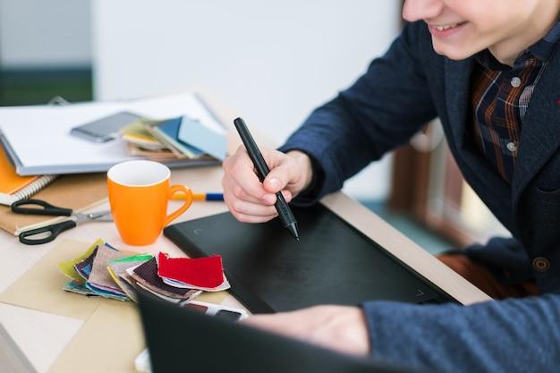 Diseñador de moda dibujando en tableta gráfica. creación de ropa nueva. ideas únicas, diseños inusuales. muestras de fábrica