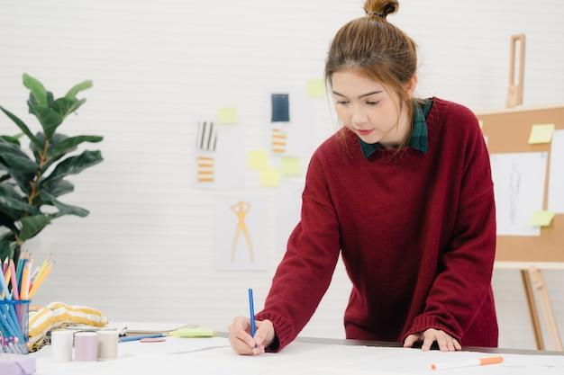 Diseñador de moda femenina asiática hermosa profesional trabajando con bocetos de tela