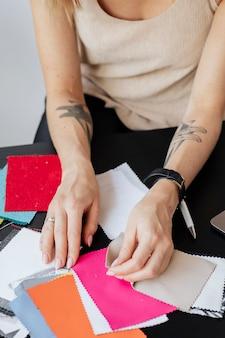 Diseñador de moda femenina eligiendo muestras de tela