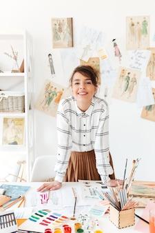 Diseñador de moda joven sonriente que se coloca en su lugar de trabajo