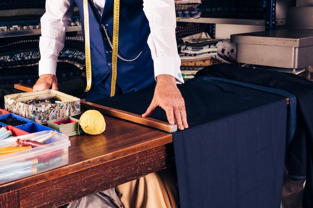 Diseñador de moda masculino senior tomando medidas de tela en mesa de madera