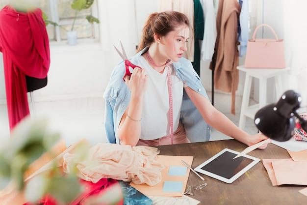 Diseñador de moda mujer trabajando en estudio sentado en el escritorio