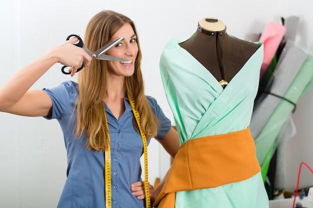 Diseñador de moda o sastre trabajando en estudio