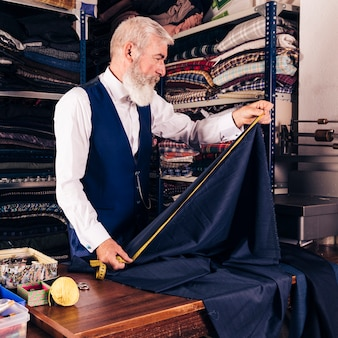 Diseñador de moda que toma la medida de la tela azul con la cinta métrica en la tabla