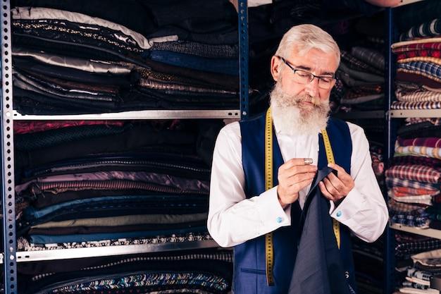 Diseñador de moda de sexo masculino joven concentrado en el trabajo en un estudio