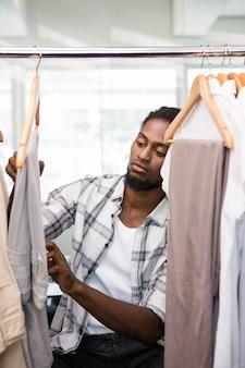 Diseñador de moda de sexo masculino que mira el estante de la ropa