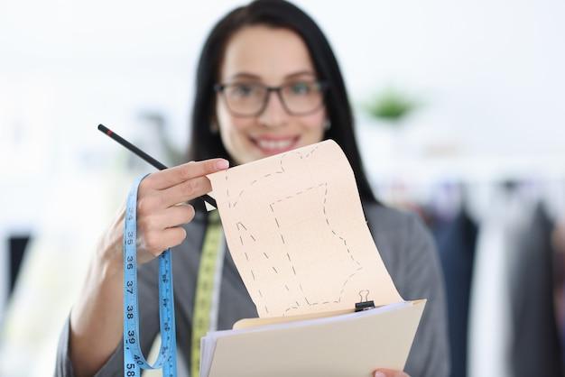 Diseñador de mujer sostiene molde con bocetos de ropa.