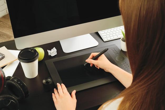 Diseñador de mujer trabajando en la oficina y usando una tableta gráfica