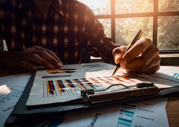 El diseñador de negocios está sosteniendo una pluma para escribir un gráfico de ingresos de inversión exitoso