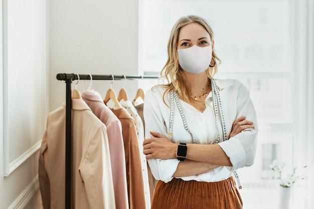 Diseñador en nueva boutique normal con máscara, covid 19