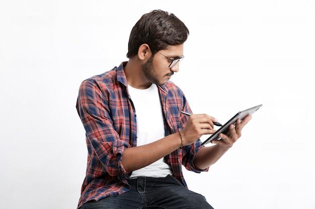 Diseñador profesional indio con tableta gráfica conectada al teléfono inteligente con lápiz digital