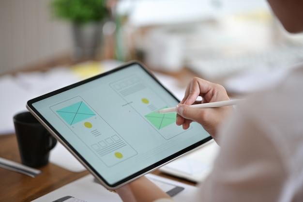 Diseñador que utiliza la planificación de tabletas wireframe en un sitio web móvil, desarrollo de aplicaciones ux ui