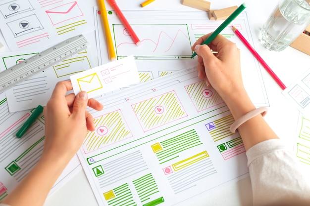 El diseñador del sitio web crea una aplicación de croquis. desarrollando un dibujo de proyecto