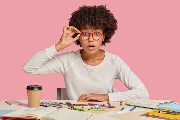 El diseñador sorprendido mantiene las manos en el borde de las gafas