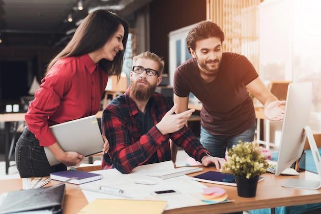 El diseñador y sus clientes están viendo la pantalla de la computadora.