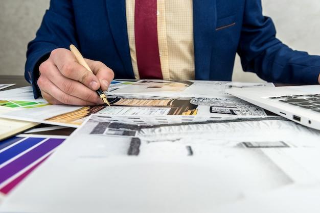 El diseñador trabaja en la oficina con un boceto creativo casero y una muestra de color para una renovación moderna. proyecto de arquitecto