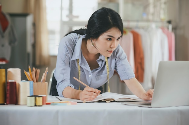 Diseñador usando computadora y dibujando bocetos para una nueva colección