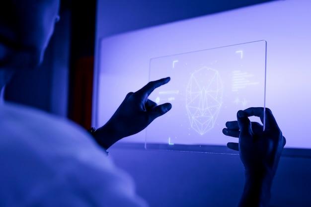 Diseñador usando una tecnología futurista de pantalla de tableta digital transparente