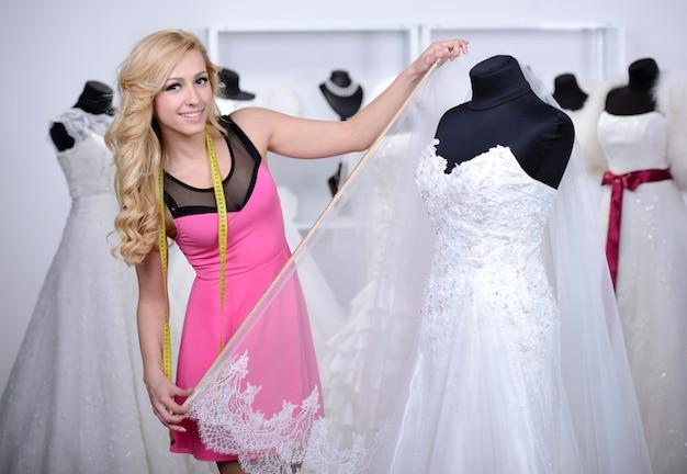 Diseñador de vestidos de novia, mide el vestido sobre un maniquí.