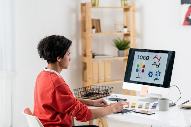 Diseñador web contemporáneo con tableta gráfica dibujando un nuevo logotipo mientras está sentado en el escritorio frente a la pantalla de la computadora