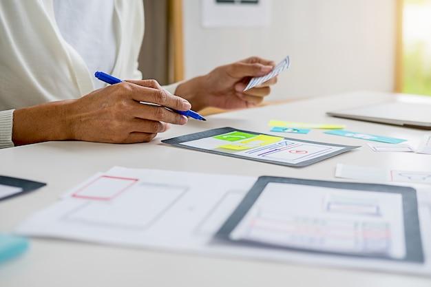 El diseñador web creativo planea la aplicación y desarrolla el diseño de plantillas, marco para teléfonos móviles.