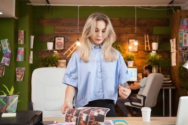 Diseñadora creativa en su oficina con un compañero de trabajo en segundo plano.