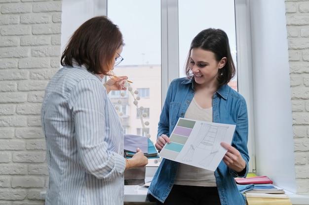 Diseñadora de interiores muestra a clienta muestras de tejidos para cortinas y tapicería