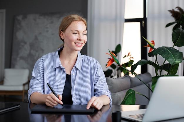 Diseñadora de logotipos trabajando en su tableta conectada a una computadora portátil