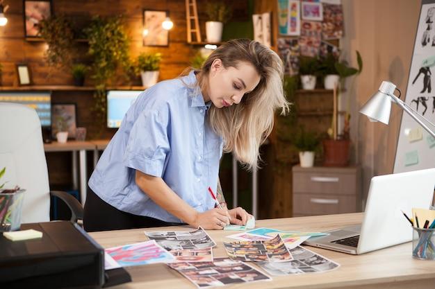 Diseñadora de moda femenina creativa tomando notas en notas adhesivas sobre materiales para la nueva línea de ropa.
