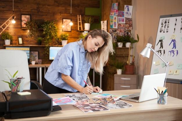Diseñadora de moda femenina creativa tomando notas en notas adhesivas.