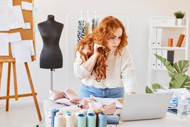 Diseñadora de moda femenina trabajando en atelier con laptop y hablando por teléfono inteligente