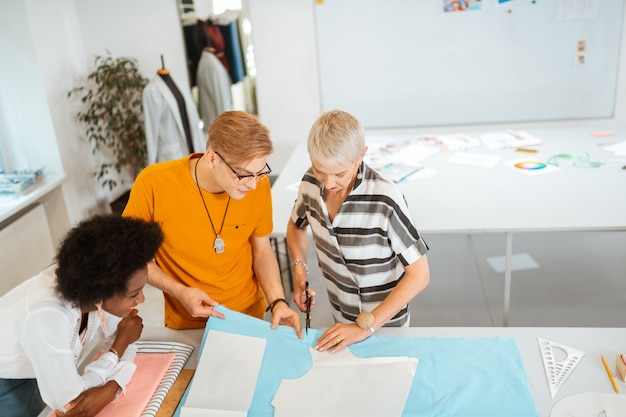 Diseñadora de moda senior cortando un patrón