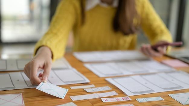Los diseñadores de aplicaciones están planificando bocetos gráficos para teléfonos inteligentes. Foto Premium