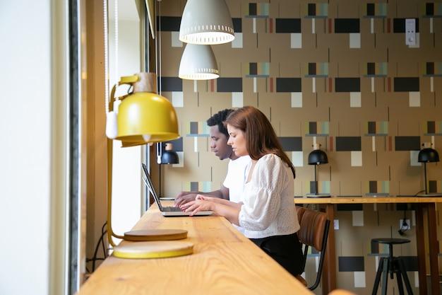 Diseñadores concentrados sentados juntos y trabajando en computadoras portátiles en el espacio de coworking