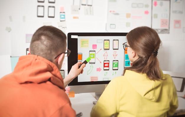 Los diseñadores desarrollan aplicaciones web para teléfonos móviles. interfaz de usuario para smartphones.