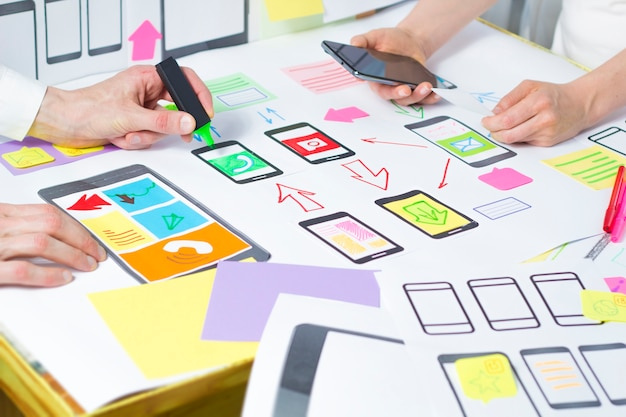 Los diseñadores desarrollan y crean aplicaciones móviles para teléfonos.