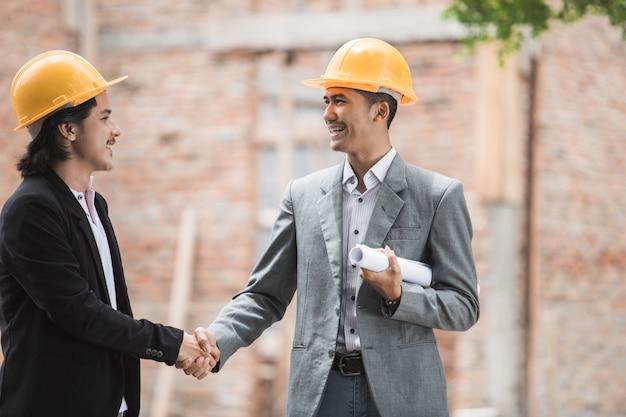 Diseñadores discutiendo el plan de construcción estrechar la mano