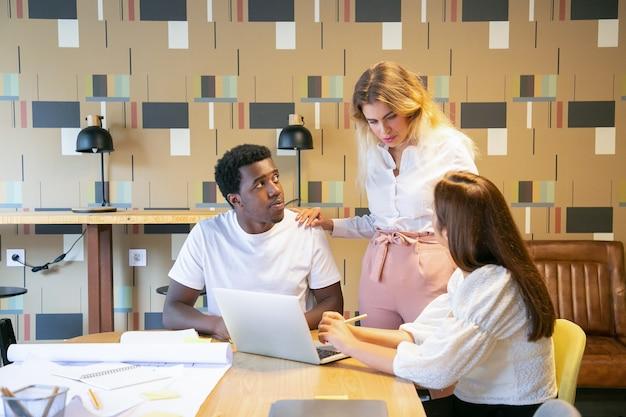 Diseñadores discutiendo el proyecto con el líder del equipo.