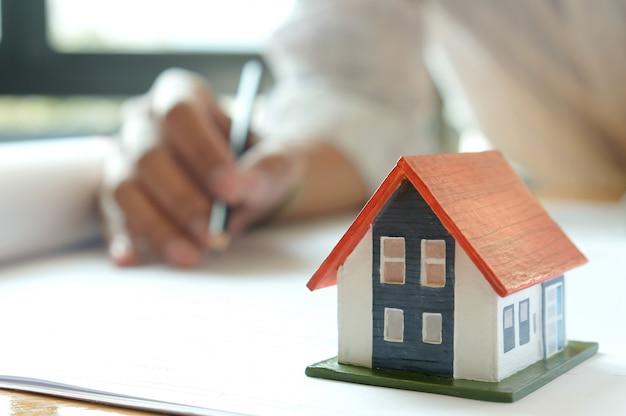 Los diseñadores están diseñando casas. casas modelo y planos de casas sobre la mesa.