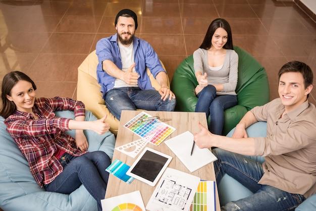 Los diseñadores están sentados a la mesa