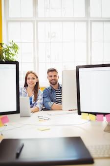 Diseñadores gráficos alegres sentado en el escritorio