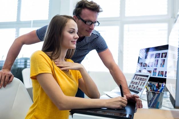 Diseñadores gráficos masculinos y femeninos que usa la tableta gráfica
