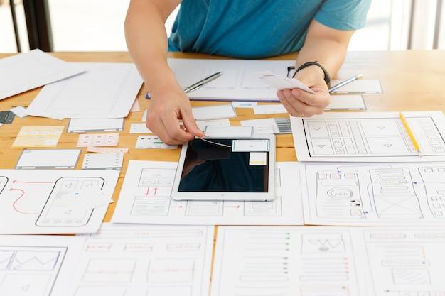 Los diseñadores gráficos trabajan junto con el marco de diseño de la plantilla de la aplicación de planificación del diseñador ux ui para el teléfono móvil, la computadora móvil