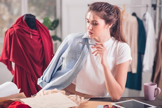 Diseñadores de moda que trabajan en estudio sentado en el escritorio