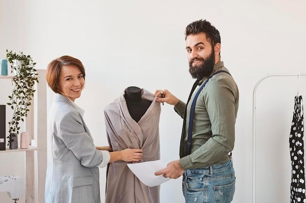 Diseñadores de moda sonrientes en atelier con forma de vestido