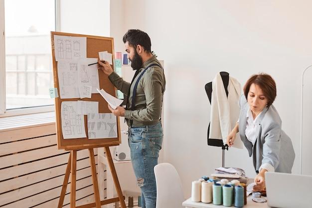 Diseñadores de moda en taller con forma de vestido y tablero de ideas.