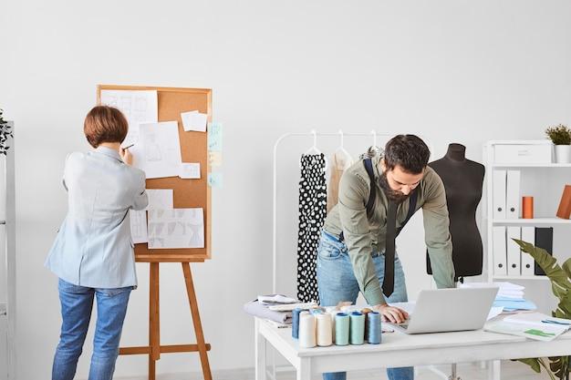 Diseñadores de moda trabajando en línea de ropa en atelier